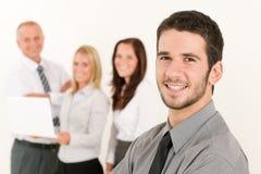 Hombre de negocios hermoso con los colegas en la parte posterior Imagen de archivo