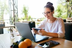 Hombre de negocios hermoso distraído de trabajo sobre el vídeo de observación del ordenador portátil en smartphone Freelancer que imagen de archivo libre de regalías
