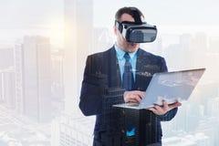 Hombre de negocios hermoso en auriculares de VR usando el ordenador portátil Fotografía de archivo