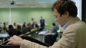 Hombre de negocios hermoso en el traje ligero que da la presentación en el podio almacen de metraje de vídeo