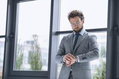 Hombre de negocios hermoso en las lentes que miran el reloj para comprobar tiempo Fotos de archivo
