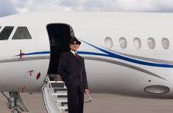 Hombre de negocios hermoso en los pasos de un jet privado Fotos de archivo libres de regalías