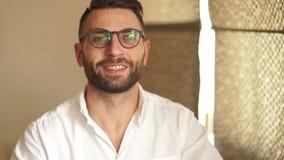Hombre de negocios hermoso en los vidrios que miran la cámara Un hombre en una camisa blanca sonríe, pone sus vidrios Hombre de n almacen de video