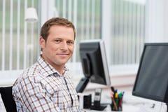 Hombre de negocios hermoso en su escritorio Imagenes de archivo