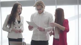 Hombre de negocios hermoso en vidrios que discute documentos con dos colegas femeninos que se colocan delante de ventana grande e almacen de video