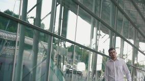 Hombre de negocios hermoso en vidrios y con la maleta en fondo moderno de la pared de cristal del terminal de aeropuerto Individu almacen de video