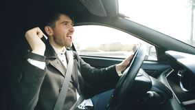 Hombre de negocios hermoso feliz que conduce el coche y que canta El hombre es feliz después de hacer tratos y conduce a casa Fotografía de archivo