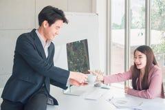 Hombre de negocios hermoso joven asi?tico y saludos hermosos de la mujer de negocios por el caf? imágenes de archivo libres de regalías