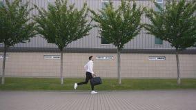 Hombre de negocios hermoso joven con la barba que corre con la maleta grande en a cámara lenta Fondo urbano de la ciudad metrajes