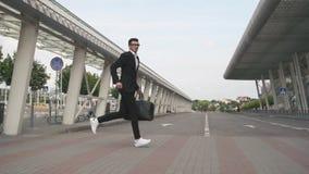 Hombre de negocios hermoso joven con la barba que corre a su aeroplano con la maleta grande en la cámara lenta Fondo urbano de la almacen de video