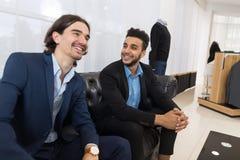 Hombre de negocios hermoso joven dos que se sienta en las compras de discurso de In Retail Store del coche foto de archivo libre de regalías