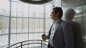 Hombre de negocios hermoso joven en el café de consumición del traje que se baja dentro de eleavator en centro de negocios modern metrajes