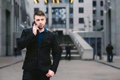 Hombre de negocios hermoso joven en un traje oscuro y el hablar en el teléfono en el fondo del paisaje urbano moderno Imágenes de archivo libres de regalías