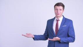 Hombre de negocios hermoso joven feliz que habla mientras que muestra algo almacen de video