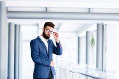 Hombre de negocios hermoso joven Posing At Workplace fotos de archivo