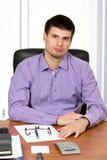 Hombre de negocios hermoso joven que se sienta en su escritorio Fotos de archivo libres de regalías