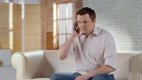 Hombre de negocios hermoso joven que tiene conversación telefónica seria con el socio fotos de archivo