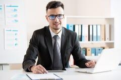Hombre de negocios hermoso joven que trabaja en una oficina fotos de archivo libres de regalías
