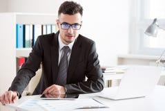 Hombre de negocios hermoso joven que trabaja en una oficina fotos de archivo