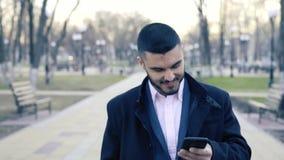 Hombre de negocios hermoso joven Standing en la calle y usar su Smartphone metrajes
