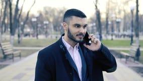 Hombre de negocios hermoso joven Standing en la calle y usar su Smartphone almacen de video