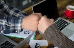 Hombre de negocios hermoso joven usando la mano a la colisión del puño imagenes de archivo
