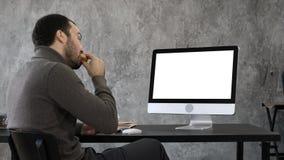 Hombre de negocios hermoso que come y que tiene una videoconferencia con alguien Visualización blanca imagen de archivo