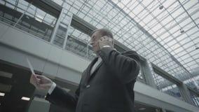 Hombre de negocios hermoso que habla en el teléfono en el aeropuerto almacen de metraje de vídeo