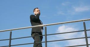 Hombre de negocios hermoso que habla en el teléfono Hombre elegante del teléfono que invita al teléfono móvil en ciudad Hombre de almacen de video