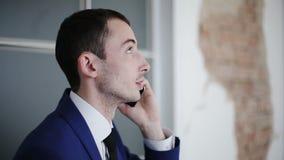 Hombre de negocios hermoso que habla en el teléfono y que mira para arriba almacen de metraje de vídeo