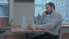 Hombre de negocios hermoso que habla en el teléfono y que trabaja con el ordenador portátil en café almacen de video
