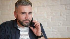 Hombre de negocios hermoso que habla en el tel?fono en el caf? Individuo barbudo joven que sostiene su smartphone cerca de su o?d almacen de video