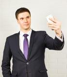 Hombre de negocios hermoso que hace la foto del selfie en smartphone imagenes de archivo