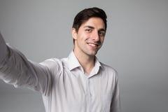 Hombre de negocios hermoso que hace la foto del selfie en smartphone sobre fondo gris foto de archivo