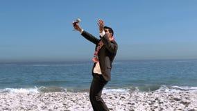 Hombre de negocios hermoso que lanza su cartera en el aire almacen de video