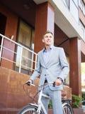 Hombre de negocios hermoso que monta una bicicleta en el fondo urbano Concepto sano de la forma de vida Copie el espacio imagen de archivo libre de regalías