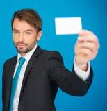 Hombre de negocios hermoso que muestra la tarjeta de visita en blanco Foto de archivo libre de regalías