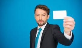Hombre de negocios hermoso que muestra la tarjeta de visita en blanco Fotografía de archivo libre de regalías