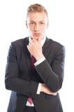 Hombre de negocios hermoso que piensa mientras que toca su barbilla fotografía de archivo