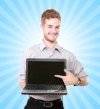 Hombre de negocios hermoso que presenta usando el ordenador portátil con la pantalla en blanco Fotos de archivo libres de regalías