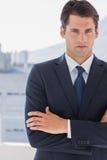 Hombre de negocios hermoso que se coloca con los brazos cruzados Imagenes de archivo