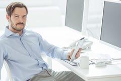 Hombre de negocios hermoso que se sienta delante de monitores Foto de archivo