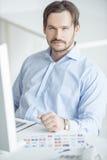 Hombre de negocios hermoso que se sienta en el escritorio Fotos de archivo libres de regalías