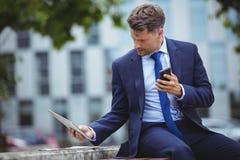 Hombre de negocios hermoso que sostiene el teléfono móvil mientras que usa la tableta digital Imagen de archivo