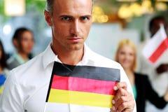 Hombre de negocios hermoso que sostiene la bandera de Alemania Imagen de archivo