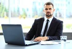 Hombre de negocios hermoso que trabaja con el ordenador portátil Fotos de archivo libres de regalías