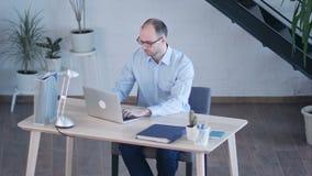 Hombre de negocios hermoso que trabaja con el ordenador portátil en oficina metrajes