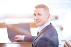 Hombre de negocios hermoso que trabaja con el ordenador portátil en oficina Fotografía de archivo