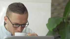 Hombre de negocios hermoso que trabaja en el ordenador portátil almacen de metraje de vídeo