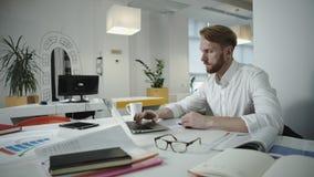 Hombre de negocios hermoso que trabaja en la oficina y que mira el marco de la foto almacen de metraje de vídeo